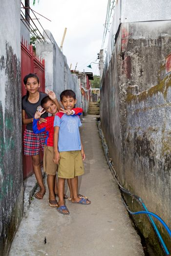 Three children, one girl and two boys, walking home down a concrete walkway in an alley guarded by tall cement and concrete block walls.