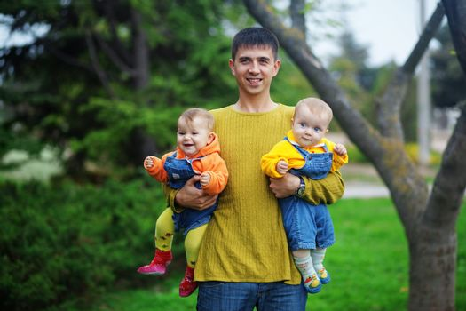 Portrait of happy young father with his two babies twins outdoor