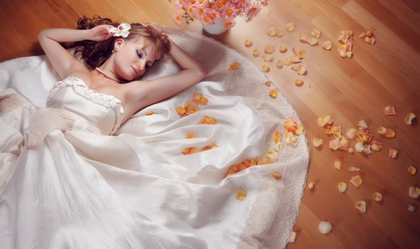 Portrait of beautiful bride lying on the floor