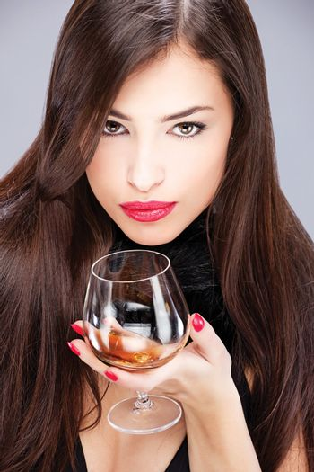 woman with pelt holding glass of brandy