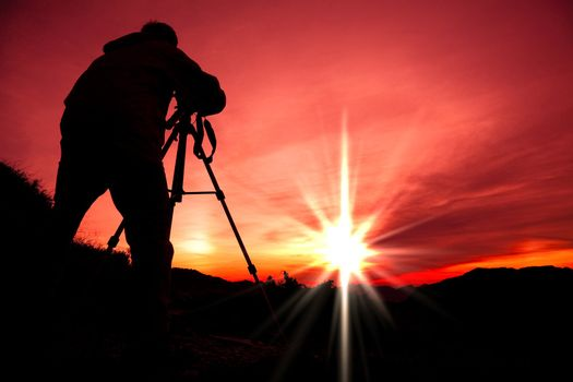 Silhouette of photographer on the top of mountain