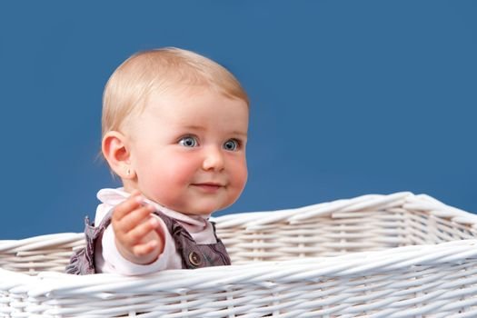 Blue eyed baby girl with relaxed expression sitting in a white basket with blue background.