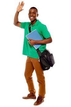 Cheerful student waving his hands. Enjoying himself
