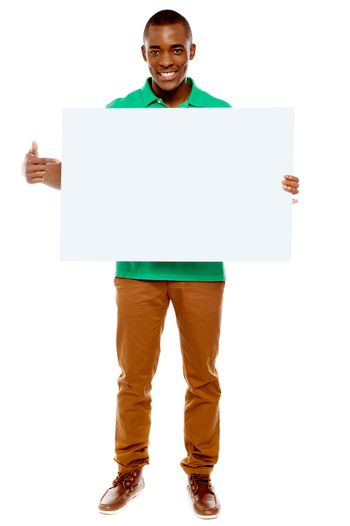 Casual young guy pointing towards placard