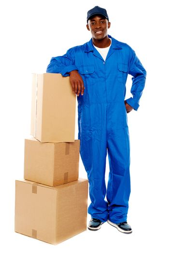 Courier boy standing beside boxes