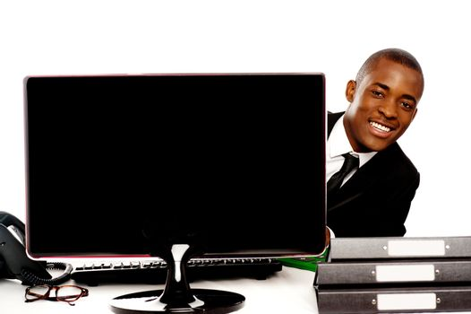 Businessman peeping from behind lcd monitor