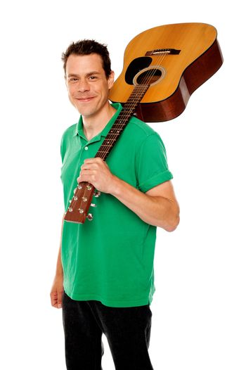 Handsome casual man with guitar on shoulders