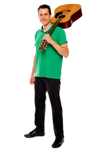 Casual music lover carrying guitar on his shoulders
