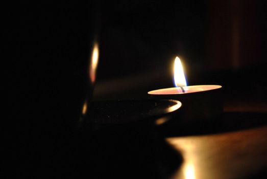 Alight candle with cup in the dark, photo