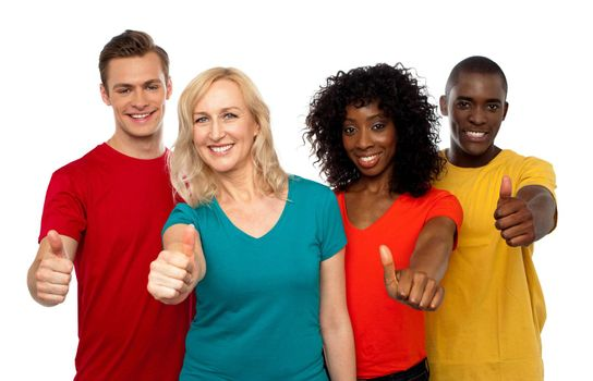 Smiling team of young people showing thumbs up