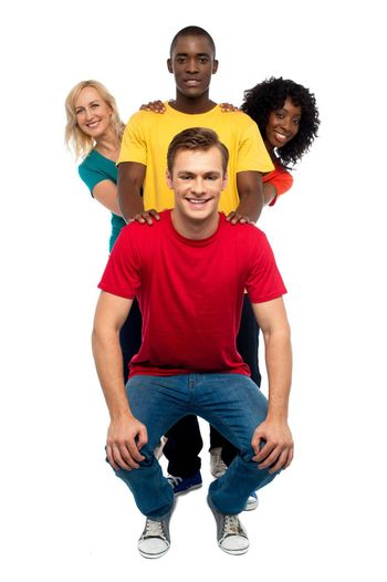 Young people standing behind semi seated guy