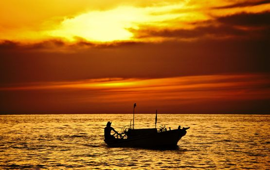 Fisherman on the boat over dramatic sunset