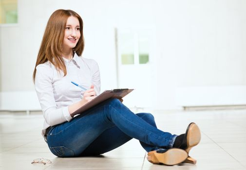 Portrait of an attractive woman sitting on the floor cross-legged and holds the tablet for notes