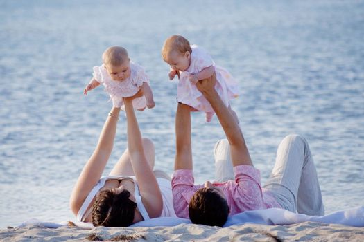 Happy family with two infant children resting on beach