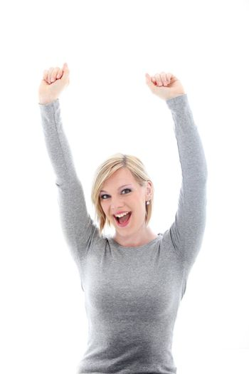 Jubilant young woman raising her arms above her head in celebration of a success isolated on white