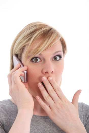 Woman reacting in shock to mobile call
