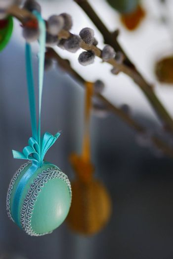 green, blue, decorated Easter egg at Easter and palm tree catkin
