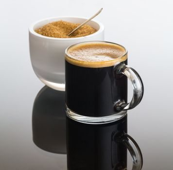 Black coffee and froth in glass mug with sugar