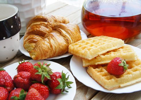 Tasty breakfast - tea, croissants, wafers with cream and strawberries
