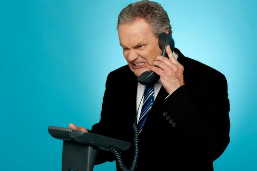 Irritated businessman communicating on phone