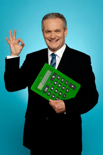 Confident executive holding calculator and gesturing okay sign