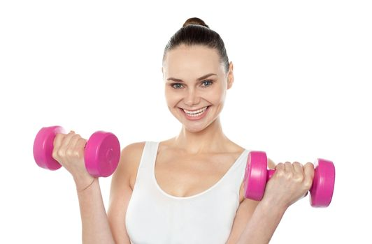 Attractive athlete exercising with dumbbells
