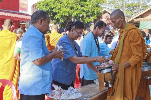 SURAT THANI, THAILAND - AUGUST 12, 2012 : Unidentified Thai peoples give food offerings to Buddhist monks during celebrated Mother's day as the birthday of Her Majesty Queen Sirikit at Chiya on August 12, 2012 in Surat Thani, Thailand.