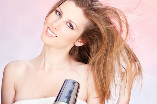 woman with towel holding blow dryer