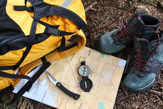 Hiking shoes on map with compass
