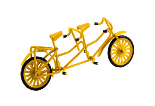 Double yellow color bicycle toy isolated on white background. Small object decor.