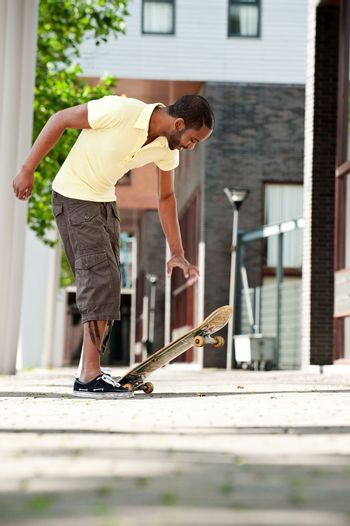 Young Black Male Kicking up a  Skateboard