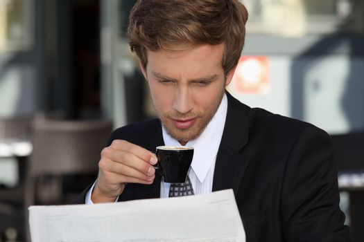 Businessman reading documents and drinking expresso