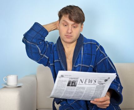 Person reads a newspaper with pensiveness