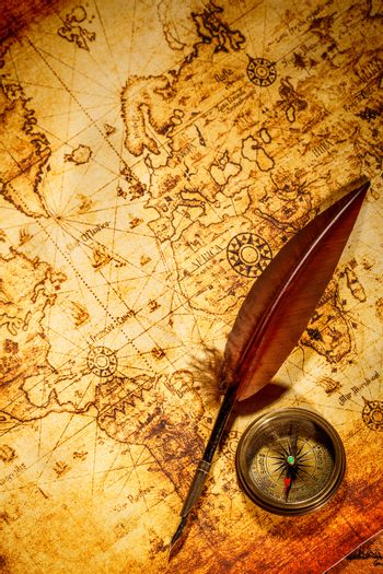 Vintage compass and goose quill pen lying on an old map.