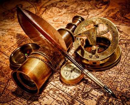 Vintage compass, goose quill pen, spyglass and a pocket watch lying on an old map.