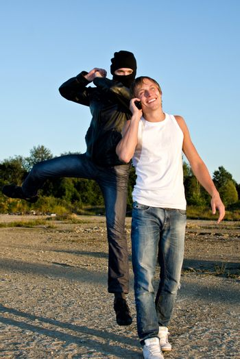Bandit in mask trying to rob young man
