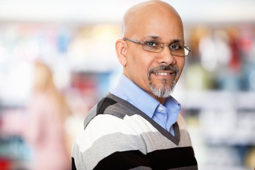 Mature man smiling while shopping in the supermarket