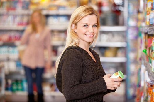 Portrait of a young woman smiling while shopping in the supermarket