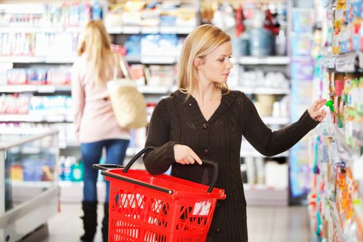 Young woman carrying basket while shopping in the supermarket