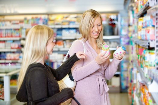 Young women smiling while shopping together in the supermarket