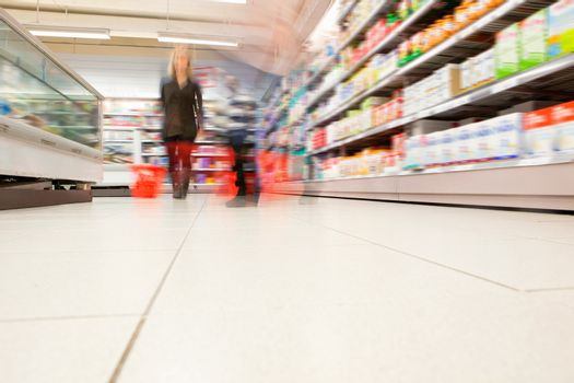 Blurred view of people in supermarket while shopping