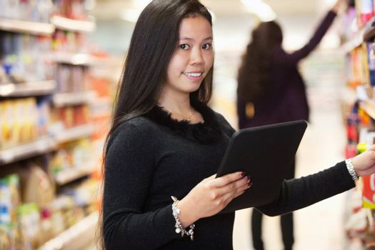 Portrait of woman looking at the products while using digital tablet in shopping centre with person in background