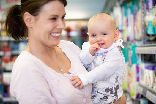 Close-up of cheerful mother and baby spending time in shopping in shopping centre, shallow depth of field of sharp focus on baby