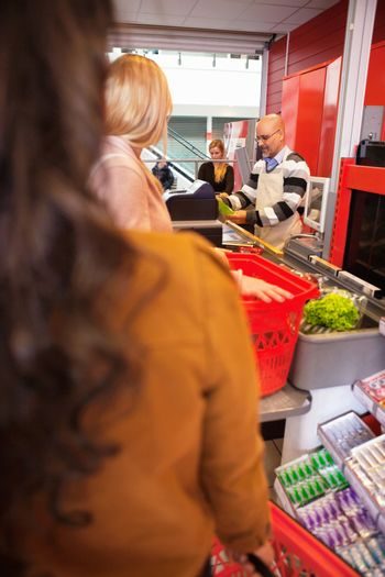 Shop assistant with customers in supermarket