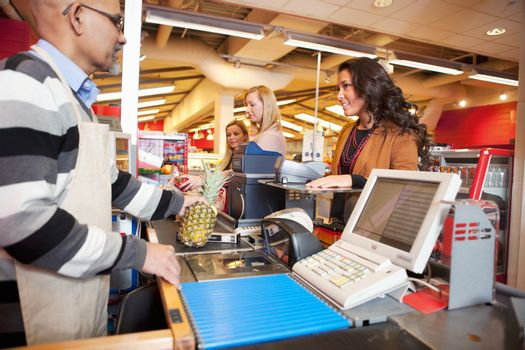 Shop assistant with customer in supermarket