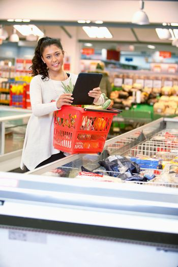 Shopper with basket holding shopping list on digital tablet and looking at camera