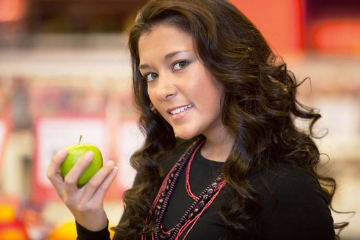 Closeup of a young woman holding apple in the supermarket