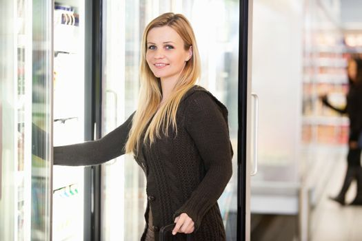 Smiling woman in front of refrigerator looking at camera with person in the background