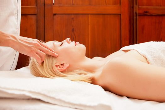 A beautiful blonde woman receiving a head and scalp massage in a spa
