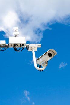 Surveillance camera on blue sky